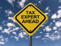 "Tax expert ahead. An yellow traffic sign with the text ""tax expert ahead"" against the blue skies Stock Image"