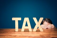 Tax fear. Accountant has a fear of the big tax. Worried or timid businessman is hiding behind the table against big taxes royalty free stock photography