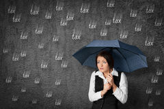 Tax fear. Accountant woman has fear of the tax. Worried businesswoman hide under umbrella against raining tax stock images