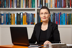 Tax financial consultant adviser accountant. Mature woman in an office or library with laptop, calculator and files binder, tax or financial accountant royalty free stock photography