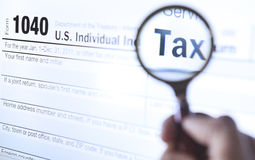 Tax form 1040. Hand holding a magnifying glass looking through tax form 1040 Stock Photos