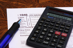 Tax Form 1040. U.S. Income Tax Form 1040 with calculator and ink pen stock photo