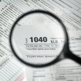 1040 tax form background. Magnifying glass showing 1040 tax form background Stock Photos