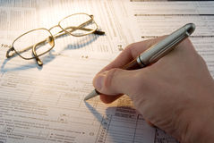 Tax form business financial concept. Hand filling in individual return tax form Stock Photo