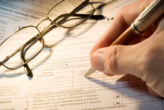 Tax form business financial concept. Hand filling in individual return tax form Stock Photos