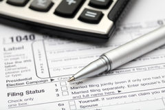 Tax Form. 1040 Tax Form with calculator and ball point pen. SDOF. Close-up Royalty Free Stock Photo