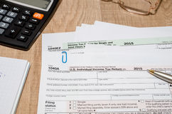1040 tax form with calculator, pen and dollar Stock Photography