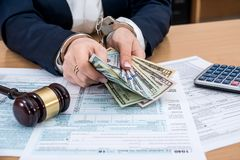 1040 tax form, dollars in hands, handcuffs and gavel royalty free stock image
