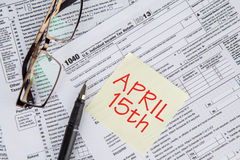 Tax form with the deadline time. Closeup of the deadline time of tax with the tax form and glasses Stock Image