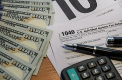 Tax form 1040, dollars, calculator and black pen on a wooden table royalty free stock photo