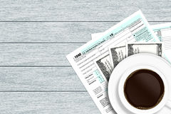 1040 tax form with dollars and coffee lying on wooden desk Stock Photography
