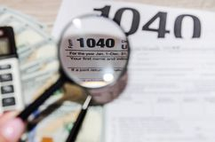 Tax form 1040, dollars, pen and magnifier on a gray, wooden table royalty free stock photo