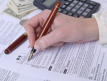 Tax form filling. Female hand filling out W-9 income tax form with pen Stock Photo