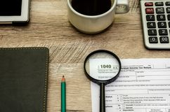 Tax form 1040, a magnifying glass. calculator and notebook. View from above. stock images