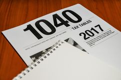 Tax form 1040 and notebook on a wooden table stock photo