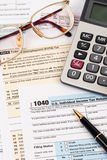 Tax form with pen, calculator, and glasses Royalty Free Stock Images