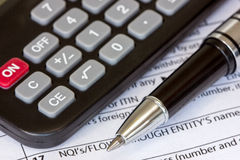 Tax form with pen and calculator Stock Photo