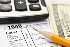Tax Form. 1040 Tax Form with pencil, calculator and one hundred dollars. SDOF. Close-up Stock Image
