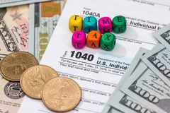Tax form with wooden cubes, dollar. Bills, coin Stock Images