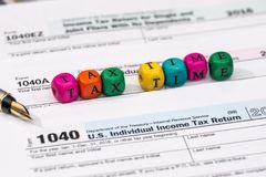 Tax form with wooden cubes, dollar bills. Coin Stock Photography