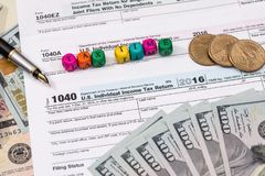 Tax form with wooden cubes, dollar bills. Coin Royalty Free Stock Images