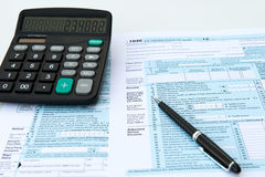 Tax forms. Filling out income tax forms with calculator and pen royalty free stock images