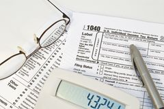 Tax Forms. Image of a calculator, glasses, and pen resting on an IRS 1040 income tax form Royalty Free Stock Images