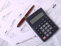 Tax forms. Calculator and ink pen laying on various american income tax forms royalty free stock photo