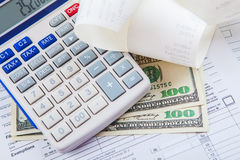 Tax forms with a calculator, bills and money Stock Image
