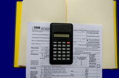 Tax forms 1040, calculator, notepad on a blue background royalty free stock photo