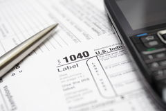 Tax forms, cell phone and pen Stock Photos