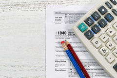 Tax forms on Desktop. Top view of U.S. Individual tax form 1040 with old calculator and pencils on wooden desktop Royalty Free Stock Image