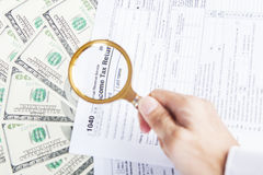 Tax forms and dollar money under magnifying glass Stock Photography