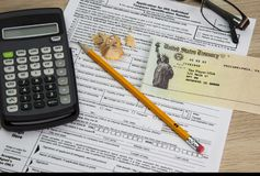 Tax Forms and Fake Check from the government. Tax time with tax forms and sinking in debt with small social security checks or Disability Check SSI. Individual royalty free stock photos