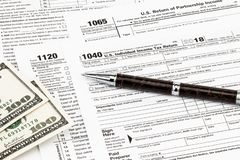 The tax forms with money and the pen. Tax Day concept stock photography