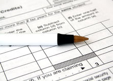 Tax forms and pen. Close-up of a white tax form ready to be filled out with a pen stock images
