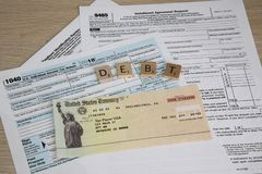 Tax Forms to File Income Tax with fake check. Tax time with tax forms and sinking in debt with small social security checks or Disability Check SSI. Individual royalty free stock images