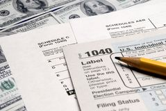 Tax Forms on top of Money. Detail closeup of current tax forms and pencil on money royalty free stock photos