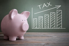 Tax increase. Chalk board tax chart with arrow pointing upwards by a piggy bank royalty free stock images
