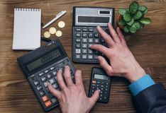 Money currency calculation. Calculator and blank note pad on office desk. Tax inspector or banker desk table background. Businessman male hands, notepad and Stock Images