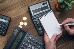 Money currency calculation. Calculator and blank note pad on office desk. Tax inspector or banker desk table background. Businessman male hands, notepad and Stock Image