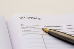 Tax invoice. A blank tax invoice with a pen lying on top of it Royalty Free Stock Photo