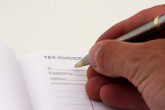 Tax invoice. A person about to wright on a tax invoice with a pen Stock Photo