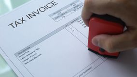Tax invoice paid, worker hand stamping seal on commercial document, business