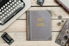 Tax Laws on old book cover at office desk with vintage items Royalty Free Stock Images