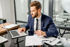 Tax manager working at the office. Handsome tax manager dressed in the suit working with documents and laptop at the modern office interior royalty free stock images
