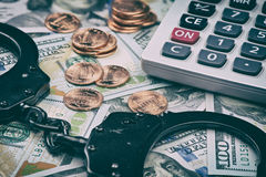 Tax offense concept. Us dollars and handcuffs Stock Photos