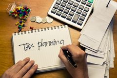Tax planning. Hand writing Tax Planning word on the accountant desk Royalty Free Stock Photography