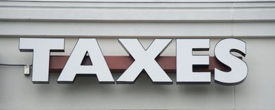 A Tax Preparation Company Sign. A sign on an tax preparation company building stock image