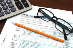 Tax Preparation - Financial IRS Individual Tax Return 1040 Form. American federal tax form 1040 with glasses, calculator and pencil isolated on white. Fill out Royalty Free Stock Photography